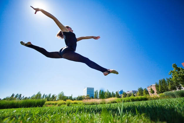 La giovane ginnasta sorridente sta saltando in spaccata e galleggia sopra la terra. Foto Premium