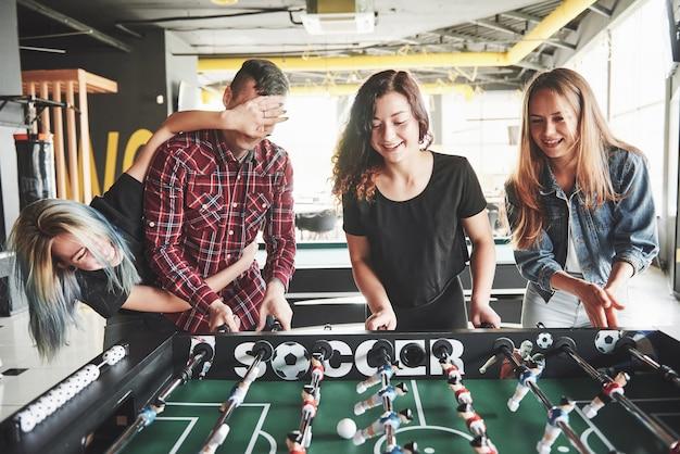 Giovani sorridenti che giocano a calcio balilla mentre sono al chiuso. Foto Premium