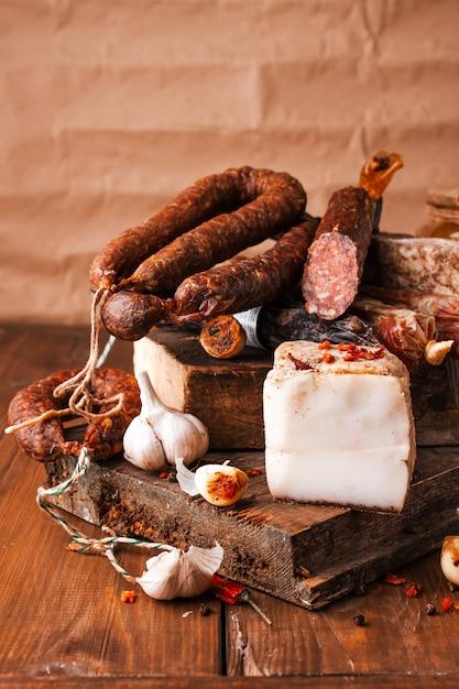 Salsiccia di maiale affumicata. costolette, pane bianco, pane di mais, fagioli, insalata di patate, ecc. varie carni affumicate e barbecue tradizionali. selezione di salumi decorati con aglio e pepe Foto Premium