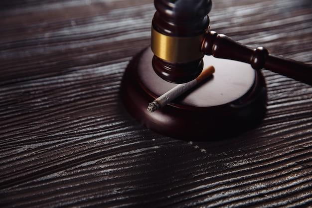 Fumo di sigaretta e primo piano in legno del martelletto del giudice. habit pericoloso Foto Premium