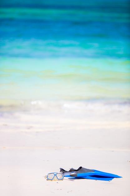 Maschera di attrezzatura per lo snorkeling, boccaglio e pinne sulla sabbia in spiaggia bianca Foto Premium