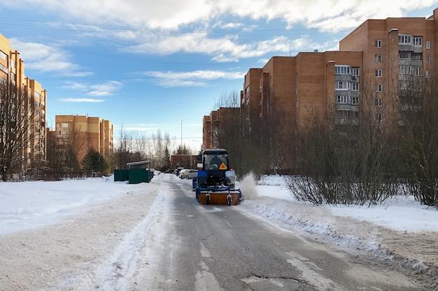 Trattore spazzaneve con uno spazzaneve pulisce la strada dalla neve nella zona residenziale in inverno Foto Premium