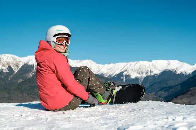 La ragazza dello snowboarder si siede con la tavola sulla pista da sci in montagna. vista posteriore. paesaggio invernale Foto Premium