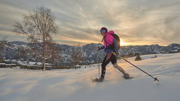 Una ragazza con le racchette da neve in un bellissimo tramonto invernale Foto Premium