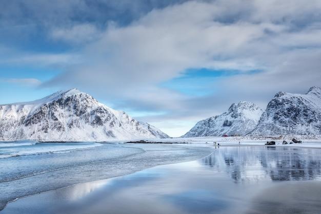 Le montagne e il cielo blu di snowy con le nuvole hanno riflesso in acqua nell'inverno Foto Premium