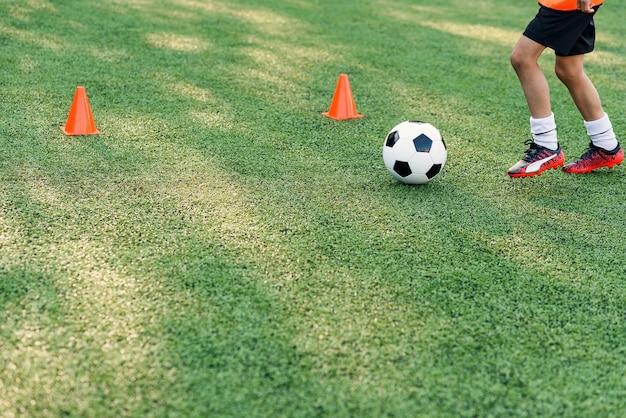 Giocatore di calcio che dà dei calci alla palla sul campo. Foto Premium