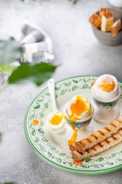 Uovo alla coque in un portauovo con pane tostato Foto Premium