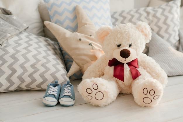 Morbido orso giocattolo e sneaker per bambino sul letto accanto ai cuscini Foto Premium