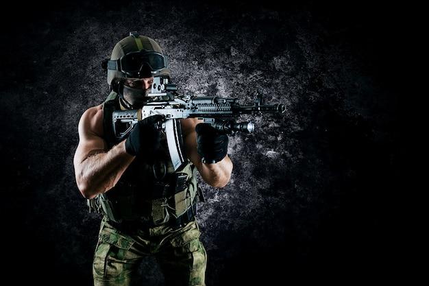 Il soldato dell'unità speciale mira alla vista del collimatore della sua mitragliatrice. tecnica mista Foto Premium