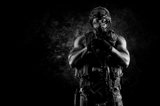 Il soldato dell'unità speciale sta con un'arma automatica a vantaggio. tecnica mista Foto Premium
