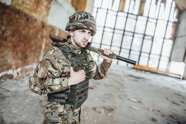 Un soldato in uniforme indossa un grosso fucile tra le mani. Foto Premium