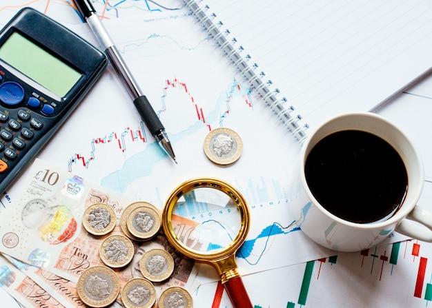 Un po 'di soldi (dollaro, centesimo, sterlina) calcolatrice, tappo di caffè, lente di ingrandimento e diversi grafici di soldi sul tavolo Foto Premium