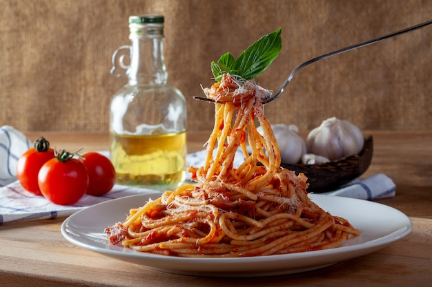 Spaghetti in un piatto su un fondo di legno Foto Premium