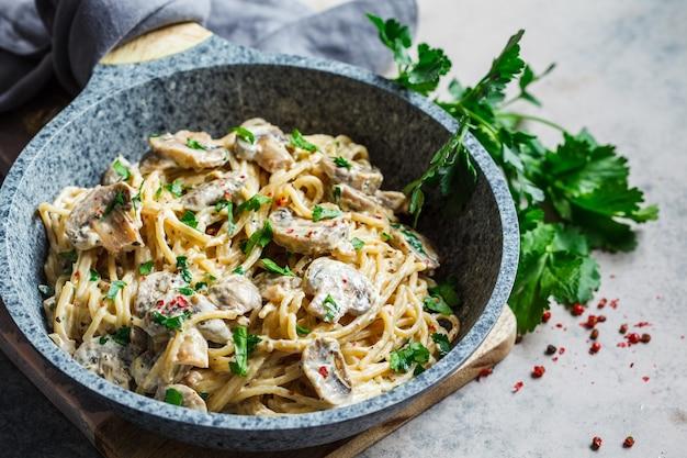 Spaghetti con salsa cremosa, funghi e prezzemolo in una padella grigia, sfondo grigio. Foto Premium