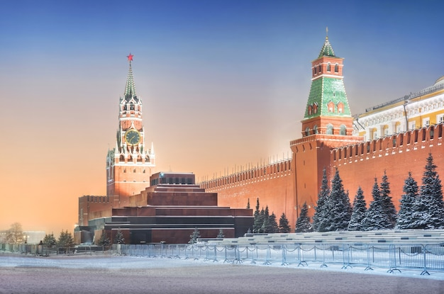 Torre spasskaya e mausoleo al cremlino di mosca e mangiato sotto la neve alla luce delle lanterne serali Foto Premium