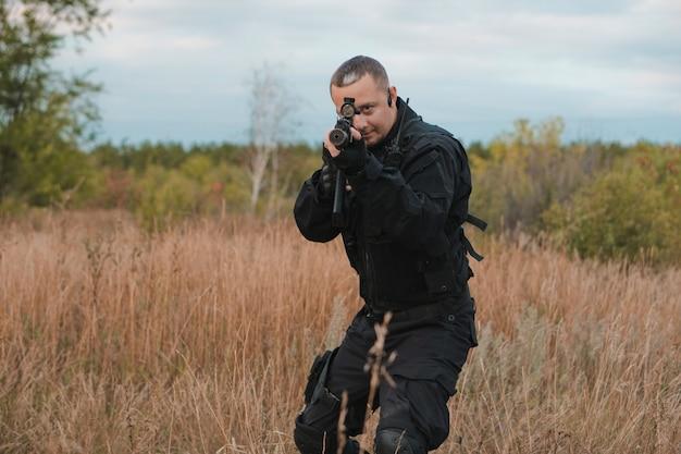 Soldato della forza speciale in uniforme nera che mira un fucile d'assalto Foto Premium