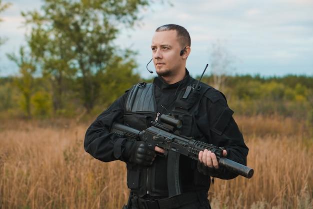 Soldato delle forze speciali in uniforme nera con un fucile d'assalto Foto Premium