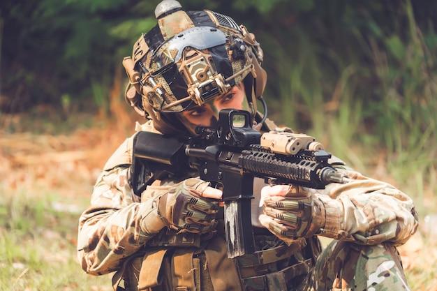 Fucile d'assalto soldato delle forze speciali con silenziatore. cecchino nella foresta. Foto Premium