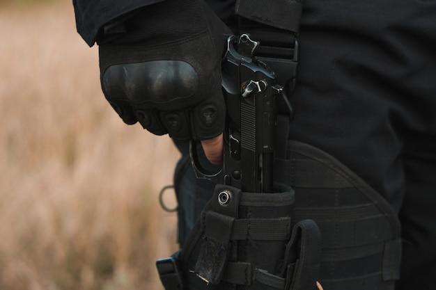 Soldato delle forze speciali in uniforme nera che tira una pistola dalla sua fondina Foto Premium
