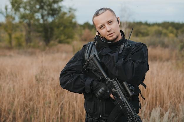Soldato delle forze speciali in uniforme nera con un fucile d'assalto che parla alla radio Foto Premium