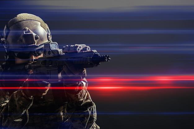 Soldato delle forze speciali con il fucile su sfondo scuro Foto Premium