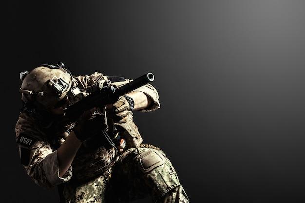Soldato delle forze speciali con il fucile su superficie scura Foto Premium