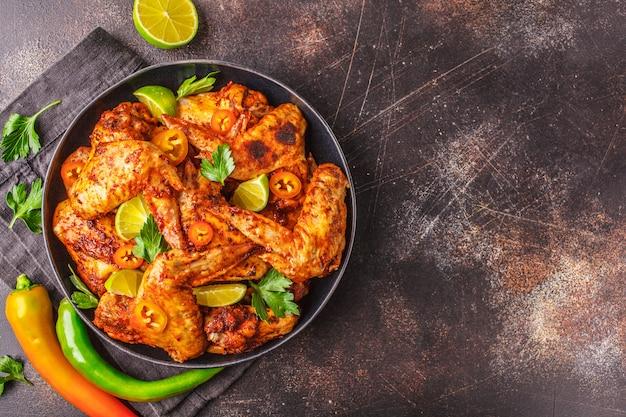 Piccante ali di pollo fritte in salsa di paprika in un piatto nero su uno spazio buio, vista dall'alto, copia dello spazio. Foto Premium