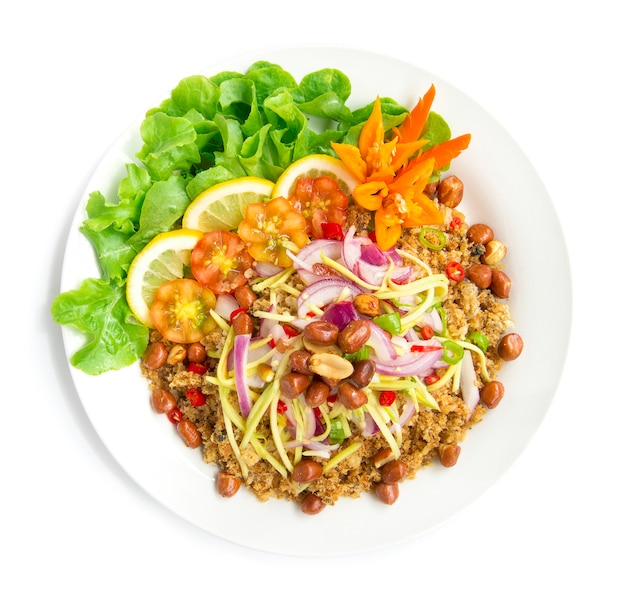 Insalata piccante pesce gatto croccante con fetta di mango cibo gustoso caldo di thai in cima arachidi fritte decorare con peperoncino di quercia verde intagliato e vista dall'alto di limone isolato su sfondo bianco Foto Premium