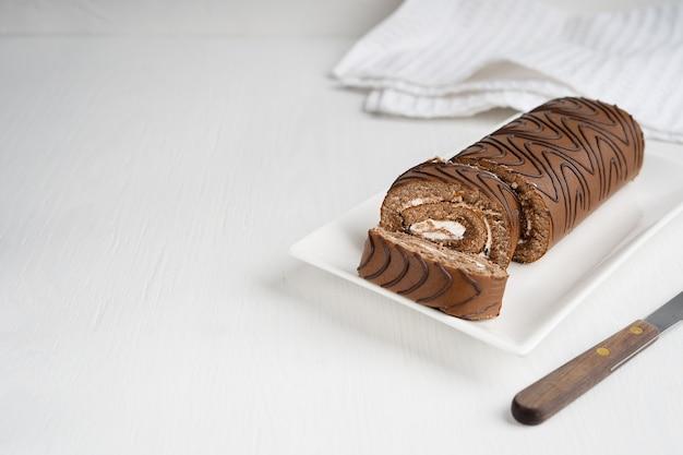 Pan di spagna o involtino con ripieno di crema affettato su piastra con coltello su sfondo di legno Foto Premium
