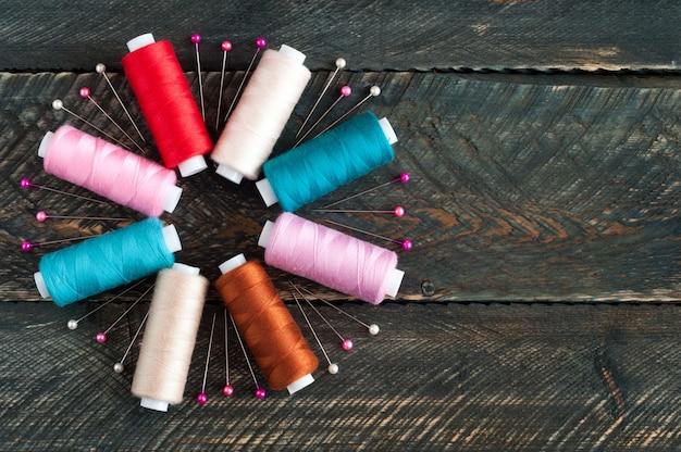 Bobine con diversi colori di filo e perni su fondo in legno vecchio. accessori da cucire Foto Premium