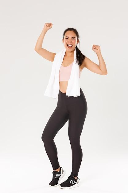 Sport, palestra e concetto di corpo sano. tutta la lunghezza della ragazza bruna asiatica felice, atleta femminile sottile in abbigliamento sportivo, gridando sì e alzando le mani motivate all'allenamento, goditi l'allenamento in palestra Foto Premium