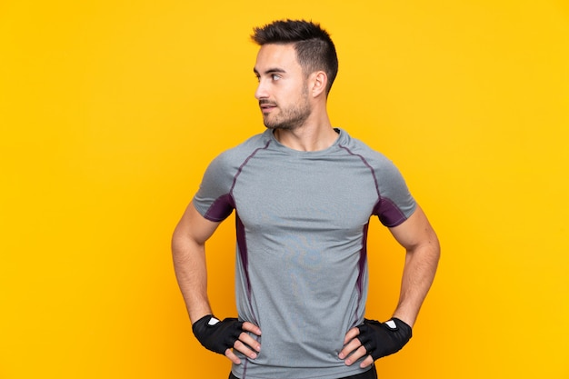 Metta in mostra l'uomo sopra la parete gialla isolata che posa con le armi all'anca e che guarda il lato Foto Premium