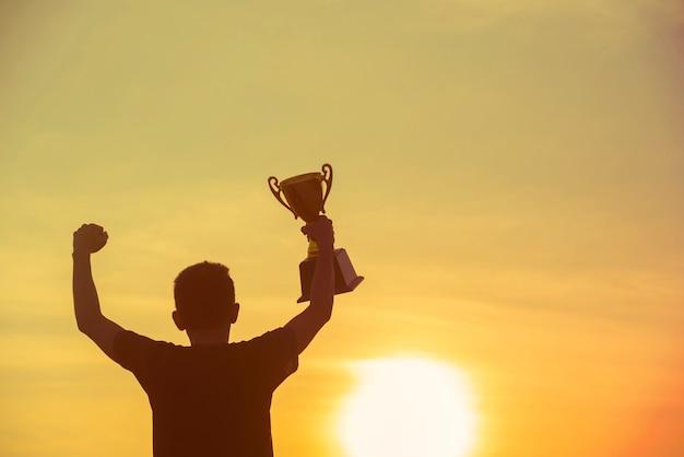 Trofeo della vittoria del vincitore del premio del vincitore del migliore uomo del trofeo della siluetta di sport per la sfida professionale il concorso del campione della coppa del trofeo d'oro vinci il premio premio per lo sport. sfida sportiva vincente Foto Premium