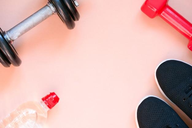 Mestieri sportivi, manubri, acqua potabile su sfondo rosa Foto Premium