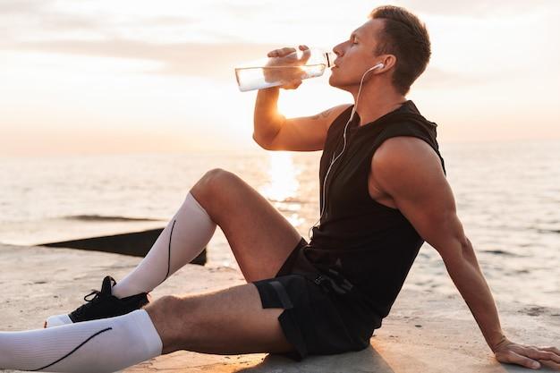 Sportivo all'aperto in spiaggia ascoltando musica con auricolari acqua potabile. Foto Premium