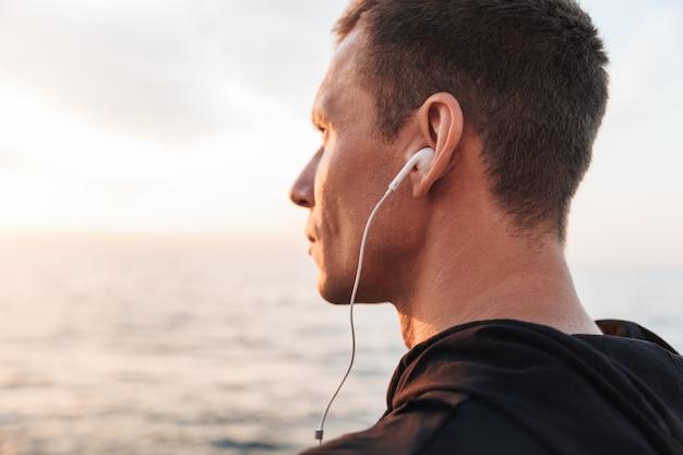 Sportivo all'aperto in spiaggia ascoltando musica con gli auricolari. Foto Premium