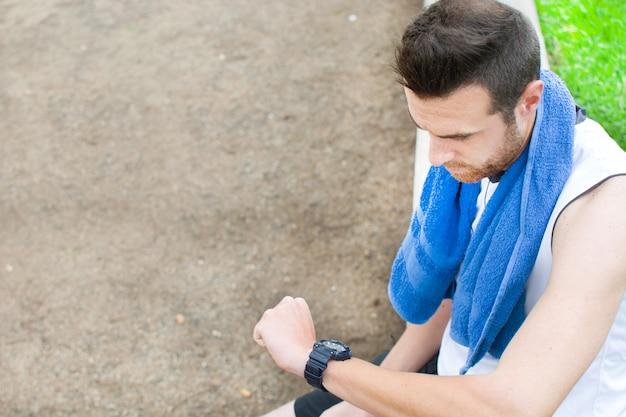 Sportivo che guarda l'orologio nel parco Foto Premium
