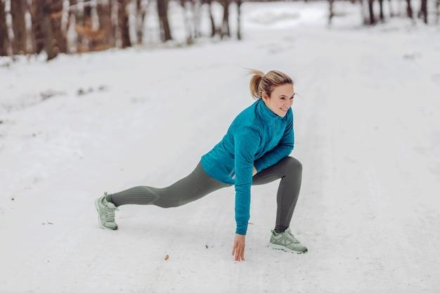 Sportiva accovacciata in natura sulla neve in inverno e facendo esercizi di riscaldamento. natura, foresta, fitness invernale, stile di vita sano Foto Premium