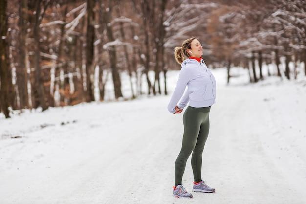 Sportiva in piedi in natura sulla neve in inverno e facendo esercizi di riscaldamento. natura, foresta, fitness invernale, stretching Foto Premium