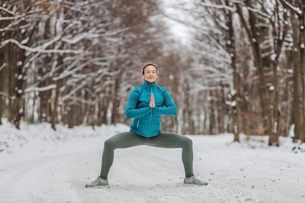 Sportiva in abito caldo facendo esercizi di yoga nella foresta innevata. fitness all'aperto, neve, freddo, fitness nella natura Foto Premium