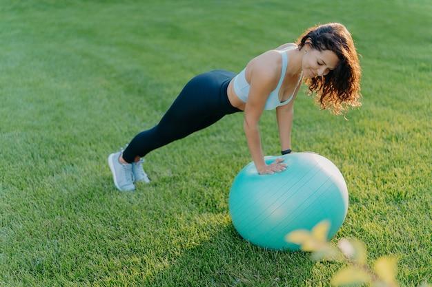 La ragazza sportiva si leva in piedi nella posa della plancia sulla palla relativa alla ginnastica Foto Premium