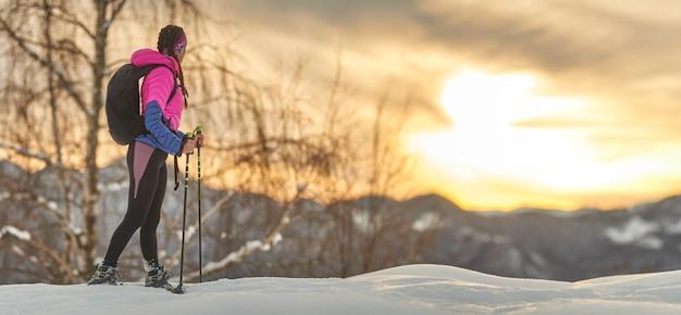 Una ragazza sportiva guarda il tramonto durante un'escursione con le ciaspole Foto Premium