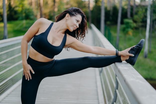 La donna castana snella sportiva vestita in top corto e leggings allunga le gambe sul ponte si riscalda prima della corsa mattutina posa all'aperto vuole avere un corpo snello e una buona salute allenarsi Foto Premium