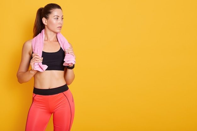 Donna piccante con un asciugamano rosa sulla spalla, in posa isolato su giallo, signora guarda da parte, copia spazio per la pubblicità. fitness, concetto di sport Foto Premium