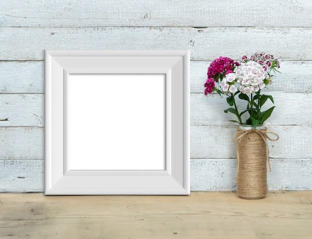 Il modello d'annata quadrato bianco della struttura di legno vicino ad un mazzo di dolce-william sta su una tavola di legno su un fondo di legno bianco dipinto. stile rustico, bellezza semplice. rendering 3d Foto Premium