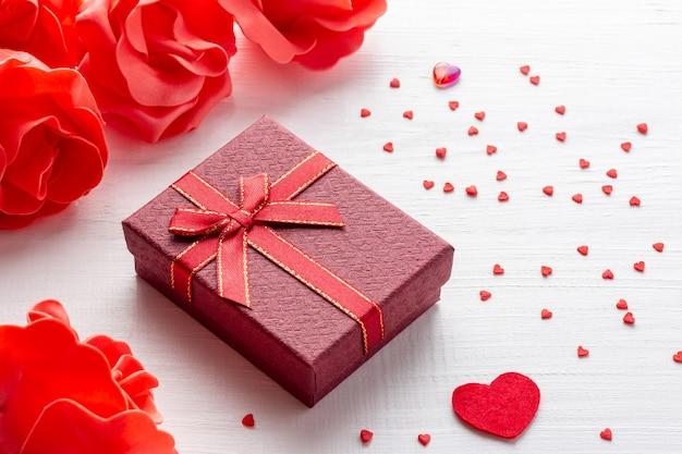 Disposizione di giorno di san valentino con scatola regalo rossa e cuori con fiori su fondo di legno bianco Foto Premium