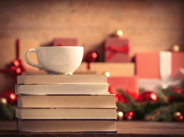 Pila di libri e tazza di caffè con regali di natale sullo sfondo Foto Premium