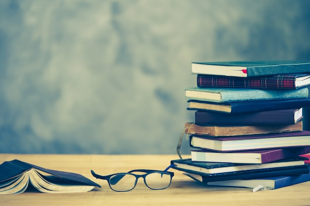 Pila di libri con gli occhiali sulla tavola di legno, spazio libero per testo, tono vintage. Foto Premium