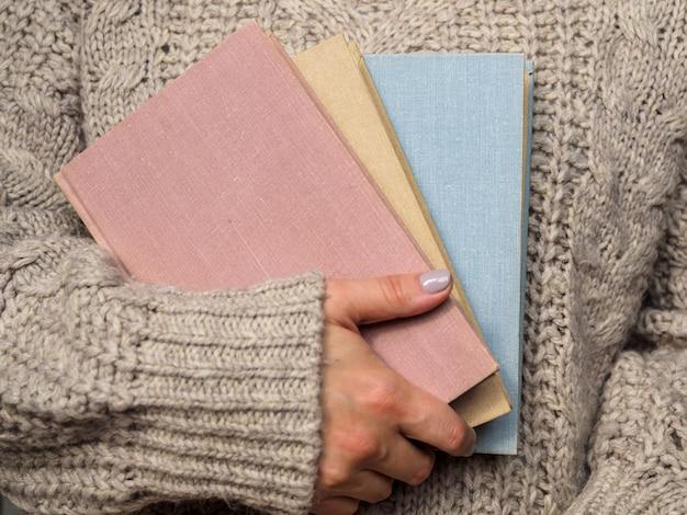 Una pila di libri nelle mani della donna Foto Premium