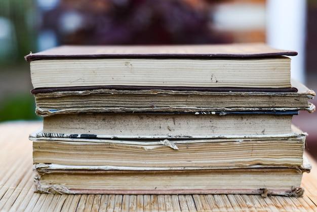 Pila di libri su una tavola di legno e bokeh verde Foto Premium